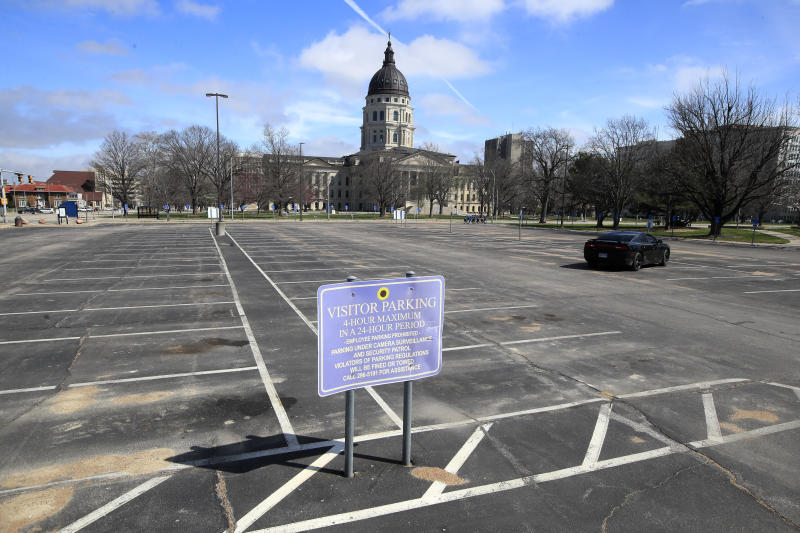 Empty parking spaces surround the Kansas Statehouse In Topeka, Kan., Wednesday, March 25, 2020. The Statehouse is closed to visitors. Shawnee County issued a stay-at-home order beginning tomorrow. (AP Photo/Orlin Wagner)