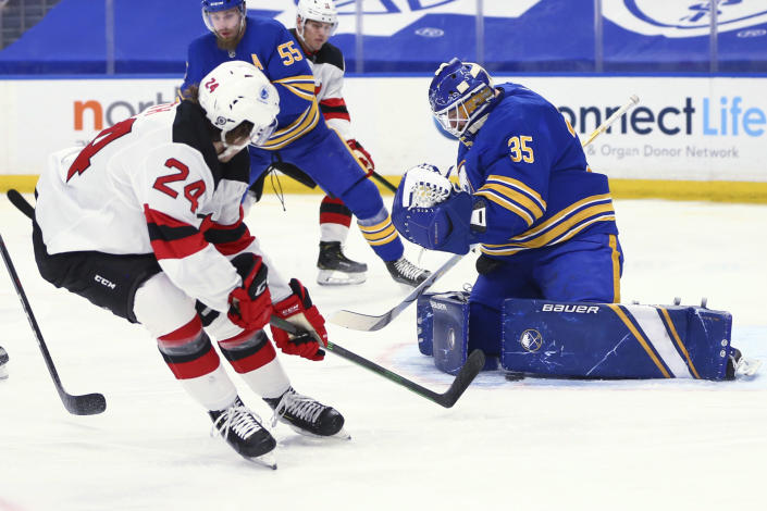 Buffalo Sabres goalie Linus Ullmark (35) stops New Jersey Devils defenseman Ty Smith (24) during the first period of an NHL hockey game Thursday, April 8, 2021, in Buffalo, N.Y. (AP Photo/Jeffrey T. Barnes)