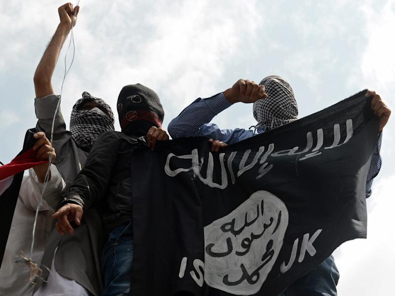 Kashmiri demonstrators hold up a flag of the Islamic State of Iraq and the Levant (ISIL) during a demonstration against Israeli military operations in Gaza, in downtown Srinagar on July 18, 2014. The death toll in Gaza hit 265 as Israel pressed a ground offensive on the 11th day of an assault aimed at stamping out rocket fire, medics said. AFP PHOTO/Tauseef MUSTAFA (Photo credit should read TAUSEEF MUSTAFA/AFP via Getty Images)