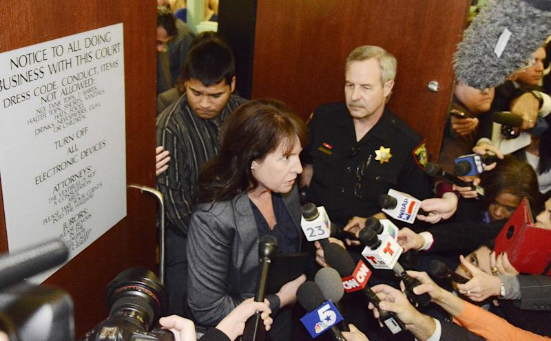 Erick Munoz, rear, husband of Marlise Munoz, stands in the doorway of the courtroom while his attorney Heather L. King answers questions from the media Friday, Jan. 24, 2014 in Fort Worth, Texas. The court ruled in Munoz's favor and to remove his brain-dead pregnant wife from life support. Judge R. H. Wallace Jr. issued the ruling in the case of Marlise Munoz. John Peter Smith Hospital in Fort Worth has been keeping Munoz on life support against her family's wishes. The judge gave the hospital until 5 p.m. CST Monday to remove life support. (AP Photo/Tim Sharp)