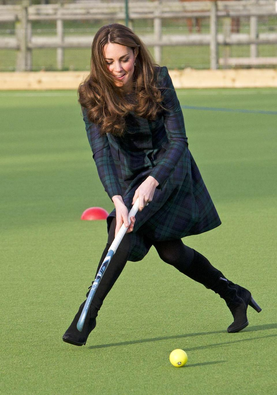 <p>Kate went back to her childhood school, St. Andrew's School, in Berkshire, England, wearing a green tartan coat dress by Alexander McQueen. And she played field hockey in heels, because that's how the duchess does. </p>