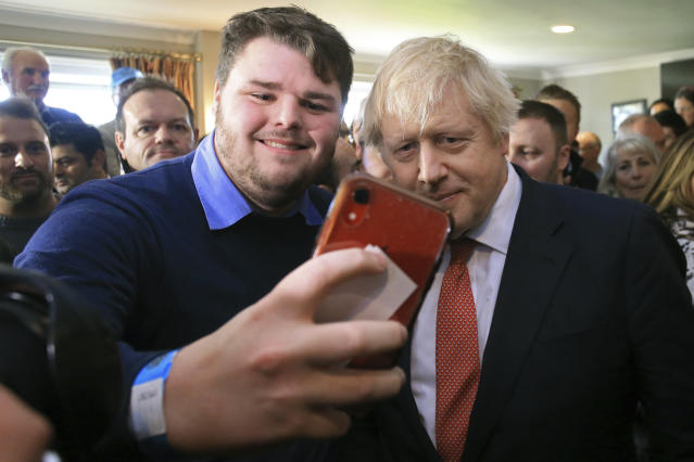 Prime minister Boris Johnson poses for a selfie with a supporter in Sedgefield on Saturday (AP)