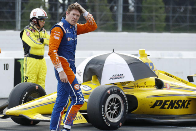 Scott Dixon walks down pit road as inclement weather delays an IndyCar Series auto race at Pocono Raceway, Sunday, Aug. 18, 2019, in Long Pond, Pa. (AP Photo/Matt Slocum)