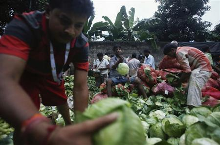 Vendors sort out cabbages along a road outside a wholesale vegetable market at dawn in Mumbai September 16, 2013. REUTERS/Danish Siddiqui