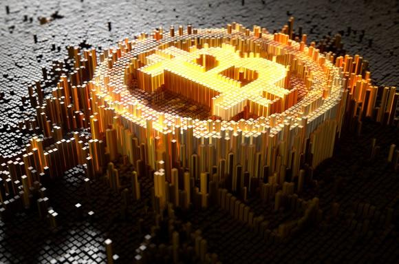 Bitcoin symbol in raised yellow mosaic against a backdrop of gray mosaic.