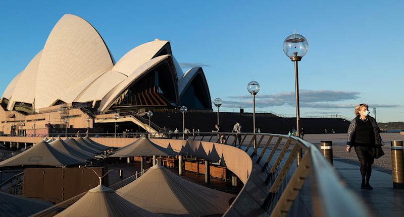 A woman is seen wearing a mask while walking in front of the Sydney Opera House
