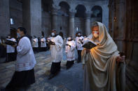 Priests circle the Edicule during Easter Sunday Mass led by the Latin Patriarch at the Church of the Holy Sepulchre, where many Christians believe Jesus was crucified, buried and rose from the dead, in the Old City of Jerusalem, Sunday, April 4, 2021. (AP Photo/Oded Balilty)