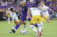 Orlando player Junior Urso, center, controls the ball among San Jose players during a MSL soccer match in Orlando, Fla., on Tuesday, June 22, 2021. (Stephen M. Dowell /Orlando Sentinel via AP)