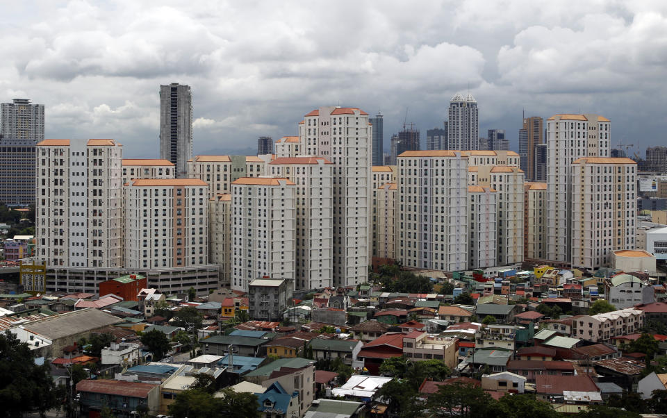 FILE PHOTO: Rows of condominium buildings are seen behind a middle-class residential district in Mandaluyong, Metro Manila July 4, 2012. One-third of the Philippines' 94 million population lives below the poverty line and infrastructure remains mostly woeful. But a growing number of analysts and investors say this time the Philippines promises to leapfrog into a higher growth pattern with signs that President Benigno Aquino is serious about tackling old problems of graft and tax dodging. The economy grew 6.4 percent in the first three months of the year, second only to China among Asian economies, and Aquino told Reuters he expected it to accelerate in the second quarter. REUTERS/Erik De Castro