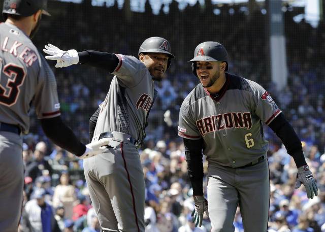 Arizona Diamondbacks' David Peralta, right, celebrates with Adam Jones, center, and Christian Walker after hitting a solo home run against the Chicago Cubs during the first inning of a baseball game Saturday, April 20, 2019, in Chicago. (AP Photo/Nam Y. Huh)