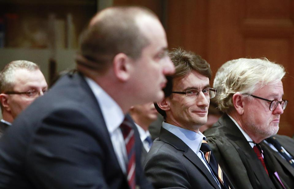 Croatian Minister Orsat Miljenic, left, Serbian First Counsellor Sasa Orbadovic, center, and William Schabas, right, prior to the start of public hearings at the International Court of Justice (ICJ) in The Hague, Netherlands, Monday, March 3, 2014. Croatia is accusing Serbia of genocide during fighting in the early 1990's as the former Yugoslavia shattered in spasms of ethnic violence, in a case at the United Nations' highest court that highlights lingering animosity in the region. Croatia is asking the ICJ to declare that Serbia breached the 1948 Genocide Convention when forces from the former Federal Republic of Yugoslavia attempted to drive Croats out of large swaths of the country after Zagreb declared independence in 1991. (AP Photo/Jiri Buller)