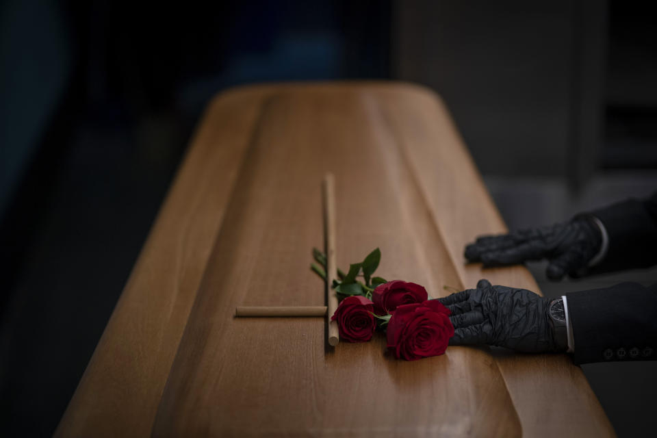 A mortuary worker prepares the coffin carrying the body of a person who died of COVID-19 before being cremated during a funeral at Mémora mortuary in Girona, Spain, Thursday, Nov. 19, 2020. (AP Photo/Emilio Morenatti)