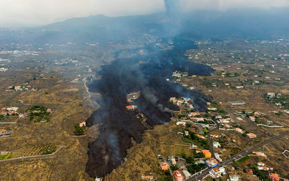 lava from a volcano eruption flows destroying houses on the island of La Palma