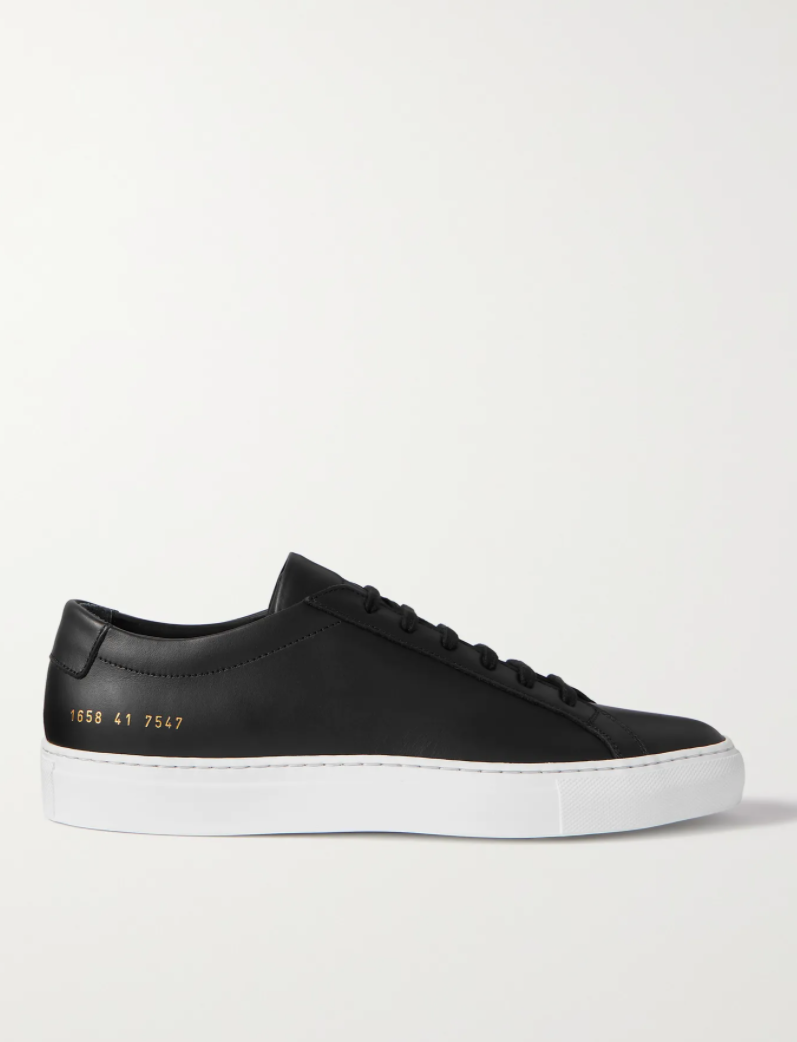 """<p><strong>Common Projects</strong></p><p>mrporter.com</p><p><strong>$435.00</strong></p><p><a href=""""https://go.redirectingat.com?id=74968X1596630&url=https%3A%2F%2Fwww.mrporter.com%2Fen-us%2Fmens%2Fproduct%2Fcommon-projects%2Fshoes%2Flow-top-sneakers%2Foriginal-achilles-leather-sneakers%2F560971904236864&sref=https%3A%2F%2Fwww.menshealth.com%2Fstyle%2Fg36283507%2Fmens-dress-sneakers%2F"""" rel=""""nofollow noopener"""" target=""""_blank"""" data-ylk=""""slk:BUY IT HERE"""" class=""""link rapid-noclick-resp"""">BUY IT HERE</a></p><p>Behold the internet darling of luxury <a href=""""https://www.menshealth.com/style/a20150491/black-shoes-men-sneakers/"""" rel=""""nofollow noopener"""" target=""""_blank"""" data-ylk=""""slk:black sneakers"""" class=""""link rapid-noclick-resp"""">black sneakers</a>, Common Projects. You'll surely spot the signature gold serial number stamped on your favorite influencer's heel or when passing a stylish netizen on the street.</p>"""