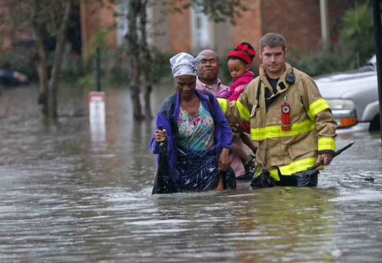 A member of the St. George Fire Department assists residents as they wade through floodwater atthe Chateau Wein Apartments in Baton Rouge, La. (Photo: Gerald Herbert/AP)