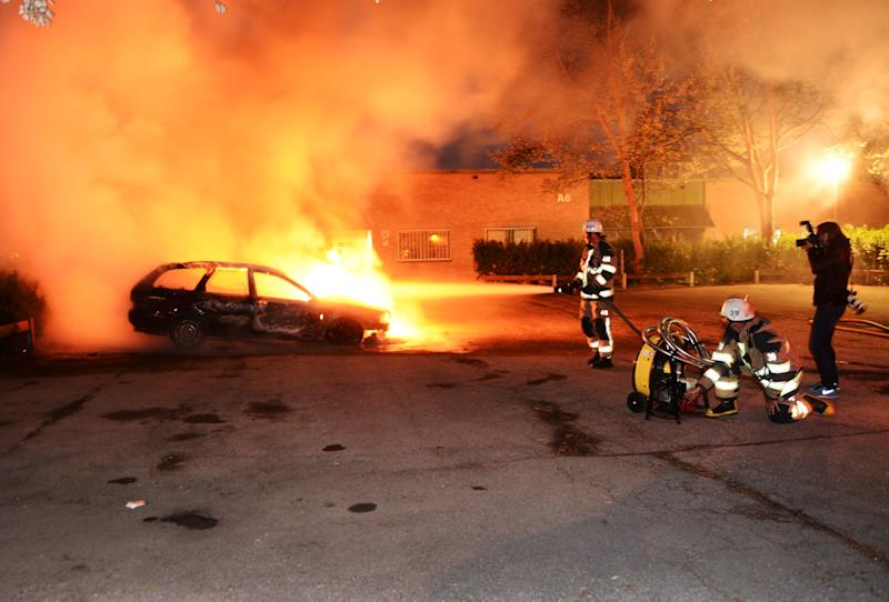 FILE - In this May 21, 2013 file photo, firemen extinguish a burning car in the Stockholm suburb of Kista after youths rioted in several different suburbs around Stockholm for a third executive night. Immigrant youth in sleepy suburban communities run amok, hurling rocks at police and torching cars, restaurants and culture centers. It isn't France or Britain, but Sweden _ a Scandinavian bastion of generous social welfare and egalitarian political culture. Though this week's rioting outside Stockholm was triggered by perceived police brutality, observers say that there has been a surge of angst in society as inequality rises on a backdrop of burgeoning immigrant numbers. (AP Photo/Scanipx Sweden, Fredrik Sandberg, File) SWEDEN OUT