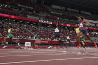Elaine Thompson-Herah, left, of Jamaica, crosses the fish line ahead of Christine Mboma, centre, of Namibia, and Gabrielle Thomas, of United States, to win the final of the women's 200-meters at the 2020 Summer Olympics, Tuesday, Aug. 3, 2021, in Tokyo. (AP Photo/David J. Phillip)