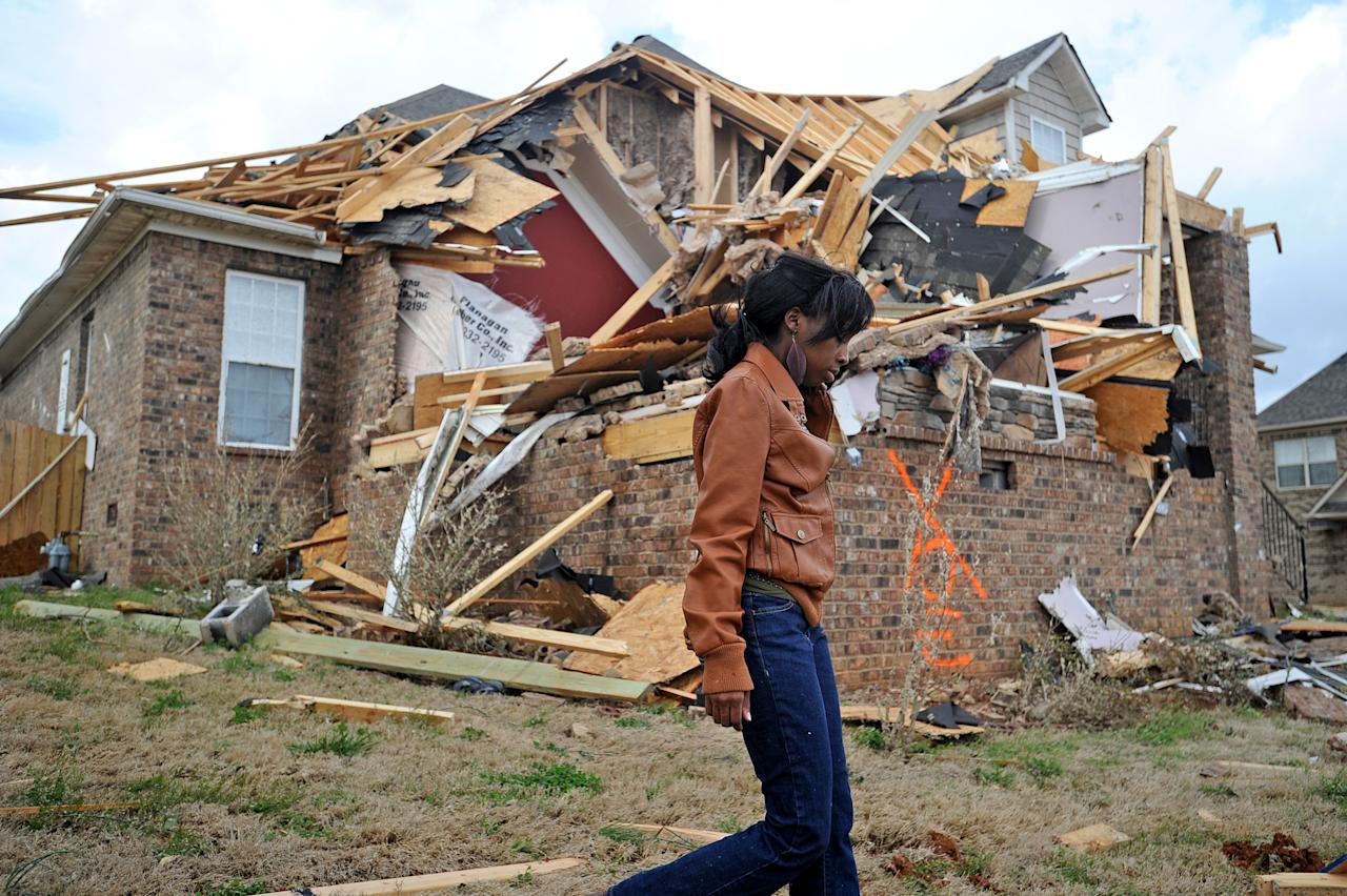 Ashley Matthews walks by her cousin's house after severe weather hit the Eagle Point subdivision in Limestone County, Ala. on Friday, March 2, 2012. A reported tornado destroyed several houses in northern Alabama as storms threatened more twisters across the region Friday (AP Photo/The Decatur Daily, Jeronimo Nisa)