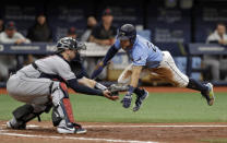 Tampa Bay Rays' Tommy Pham, right, prepares to get tagged out by Cleveland Indians catcher Kevin Plawecki while trying to score on a double by Travis d'Arnaud during the fifth inning of a baseball game Sunday, Sept. 1, 2019, in St. Petersburg, Fla. (AP Photo/Chris O'Meara)