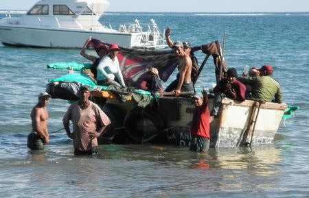 Fifteen Cuban migrants prepare to set sail in their 14-foot homemade boat after a brief overnight stop offshore Grand Cayman Island