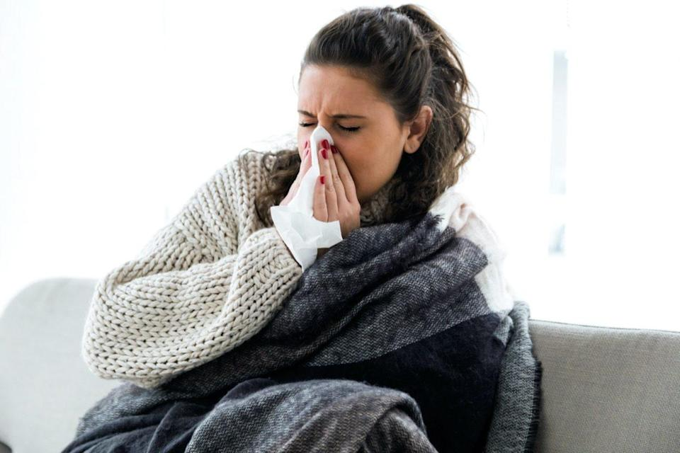 Illness young woman sneezing into a handkerchief