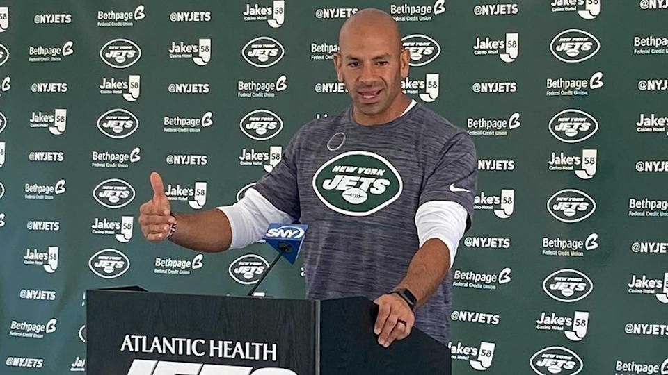 Robert Saleh speaking at podium at 2021 Jets training camp, talking with hands