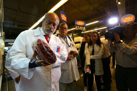 FILE PHOTO: A member of the Public Health Surveillance Agency inspects beef at a supermarket after the Chilean government suspended all meat and poultry imports from Brazil, in Santiago