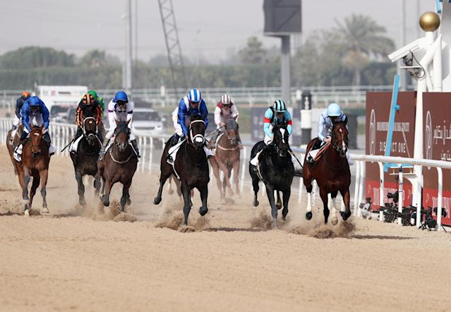 Horse Racing - Dubai World Cup 2018 - Meydan Racecourse, Dubai - United Arab Emirates - March 31, 2018 - Rayn Moore (R) rides Heavy Metal from Britain to the finish line to win the first race. REUTERS/Ahmed Jadallah