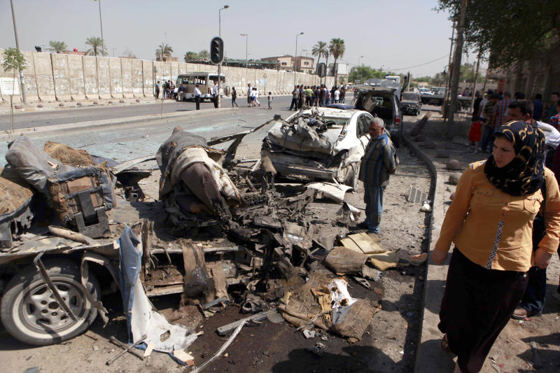 Citizens inspect the site of a car bomb attack in front of Ministry of the Higher Education and Scientific Research in central Baghdad, Iraq, Wednesday, Sept. 18, 2013. An Iraqi police officer said a parked car bomb exploded in a deadly attack on a commercial area in central Baghdad. More than 4,000 people have been killed since April, including over 804 just in August, according to U.N. figures. (AP Photo/ Hadi Mizban)