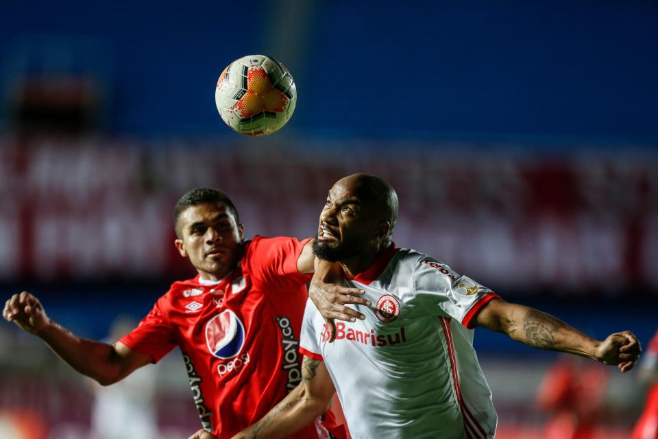 Colombia's America de Cali midfielder Carlos Sierra (L) and Brazil's Internacional defender Rodrigo Moledo vie for the ball during their closed-door Copa Libertadores group phase football match at the Pascual Guerrero Olympic Stadium in Cali, Colombia, on September 29, 2020, amid the COVID-19 novel coronavirus pandemic. (Photo by ERNESTO GUZMAN JR / POOL / AFP) (Photo by ERNESTO GUZMAN JR/POOL/AFP via Getty Images)