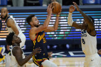 Golden State Warriors guard Stephen Curry, middle, shoots between Minnesota Timberwolves guard Anthony Edwards, left, and forward Jarred Vanderbilt (8) during the second half of an NBA basketball game in San Francisco, Wednesday, Jan. 27, 2021. (AP Photo/Jeff Chiu)