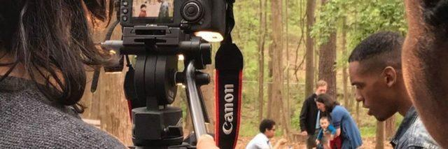 Filmmaker looking through a camera at scene in the woods