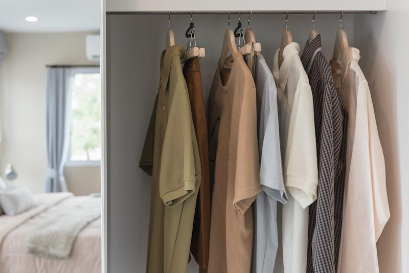 Getty Images - wooden wardrobe with clothes hanging on rail