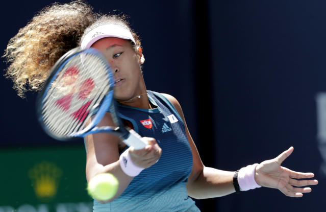 Naomi Osaka, of Japan, returns to Yanina Wickmayer, of Belgium, during the Miami Open tennis tournament, Friday, March 22, 2019, in Miami Gardens, Fla. (AP Photo/Lynne Sladky)