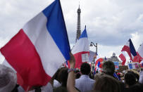 """A protestor waves a French flag with a message that reads """"stop the blackmail"""" during a demonstration in Paris, France, Saturday, July 31, 2021. Demonstrators gathered in several cities in France on Saturday to protest against the COVID-19 pass, which grants vaccinated individuals greater ease of access to venues. (AP Photo/Michel Euler)"""
