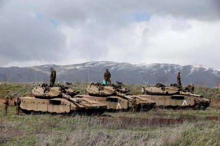 FILE PHOTO: Israeli soldiers stand atop tanks in the Golan Heights near Israel's border with Syria