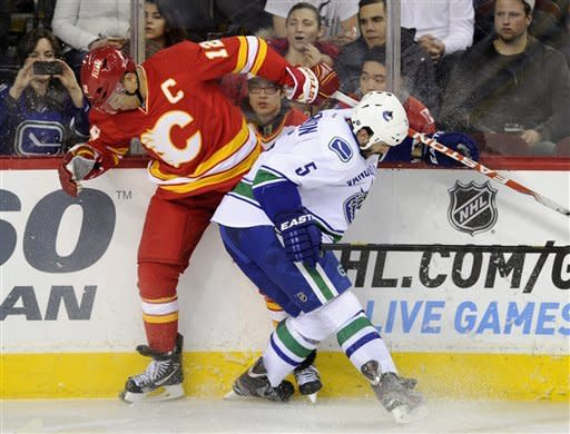Vancouver Canucks' Jason Garrison, right, battles with Calgary Flames' Jarome Iginla during second period NHL action in Calgary on Sunday, March 3, 2013. (AP Photo/The Canadian Press, Larry MacDougal)