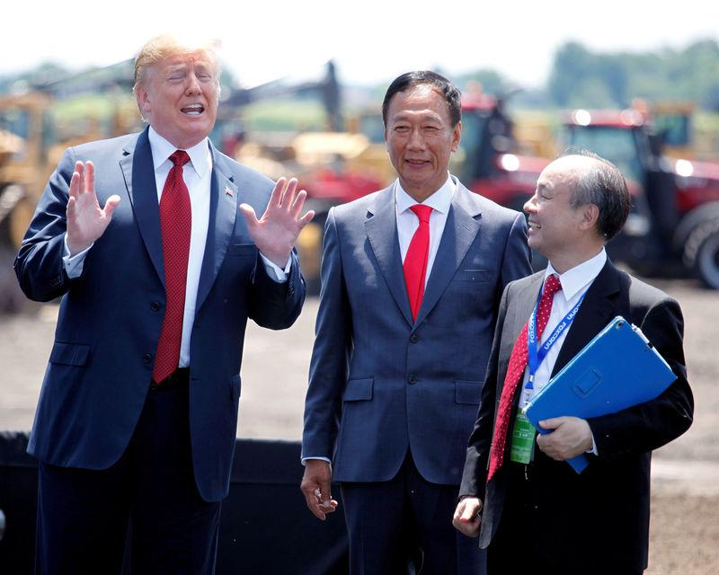 FILE PHOTO: President Donald Trump, along with Terry Gou, founder and chairman of Foxconn, and Masayoshi Son, CEO of Softbank, talk after the Foxconn Technology Group groundbreaking ceremony for its LCD manufacturing campus in Mount Pleasant