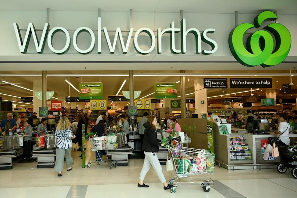 Woolworths shoppers leave checkout with groceries.