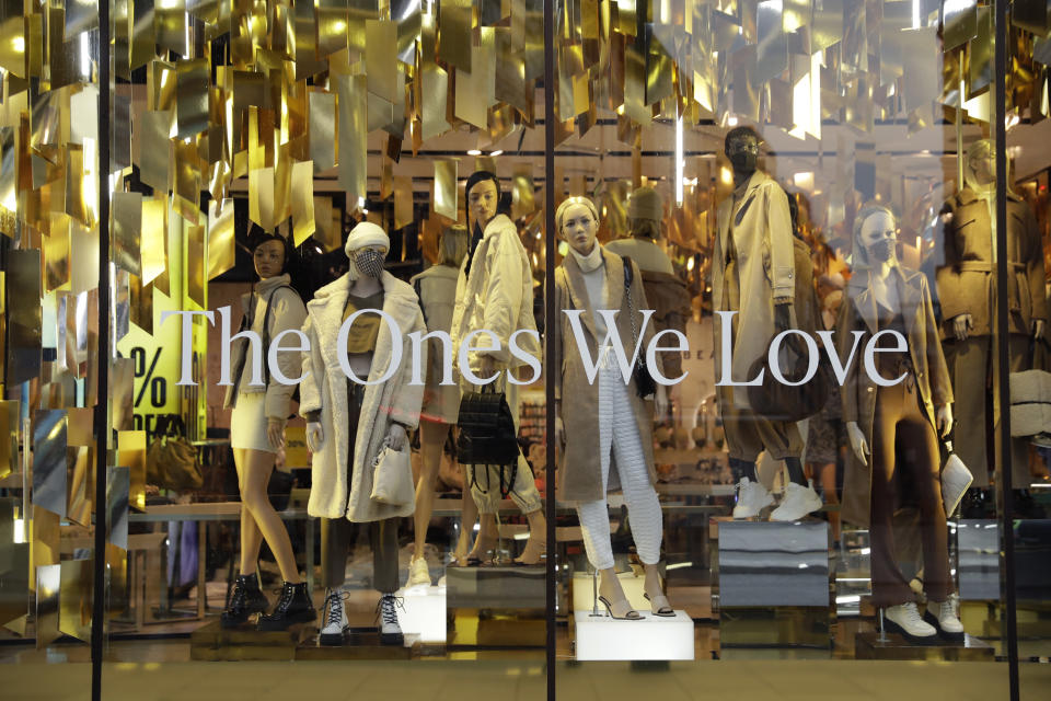 Mannequins, some wearing face masks, display clothes in the front window of the temporarily closed Topshop flagship store on Oxford Street, during England's second coronavirus lockdown, in London, Monday, Nov. 30, 2020. Arcadia Group, the retail empire of tycoon Philip Green, which owns well-known British fashion chains like Topshop and employs around 15,000 people, appears to be on the brink of collapse following the economic shock of the coronavirus pandemic. (AP Photo/Matt Dunham)