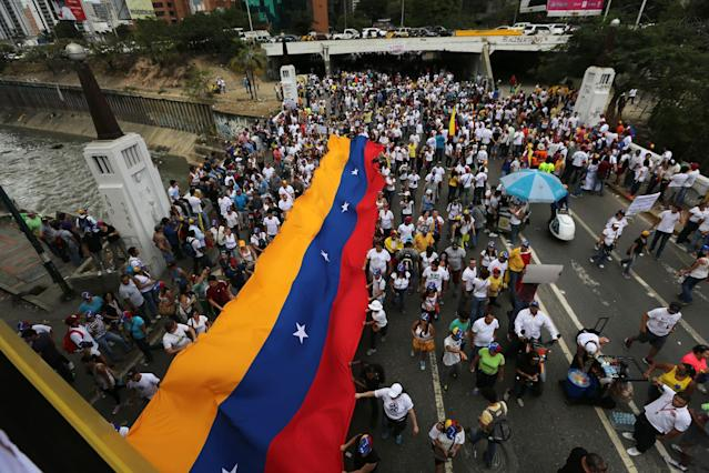 Demonstrators display a Venezuelan flag during a protest in Caracas, Venezuela, Sunday, March 2, 2014. Since mid-February, anti-government activists have been protesting high inflation, shortages of food stuffs and medicine, and violent crime in a nation with the world's largest proven oil reserves.(AP Photo/Fernando Llano)