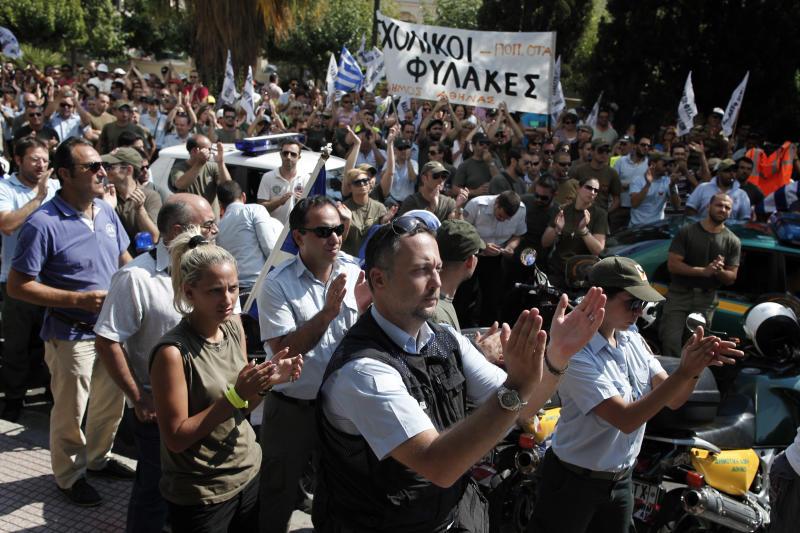 Striking municipal police officers clap hands during a protest, against new austerity cuts that will affect thousands of public sector workers, in Athens, on Friday, July 12, 2013. The measures are part of a broad plan to slash the size of Greece's bloated public sector, which counts some 670,000 employees. The government has committed to firing 15,000 people by the end of 2014 and transferring another 12,500 to new positions this year. (AP Photo/Petros Giannakouris)
