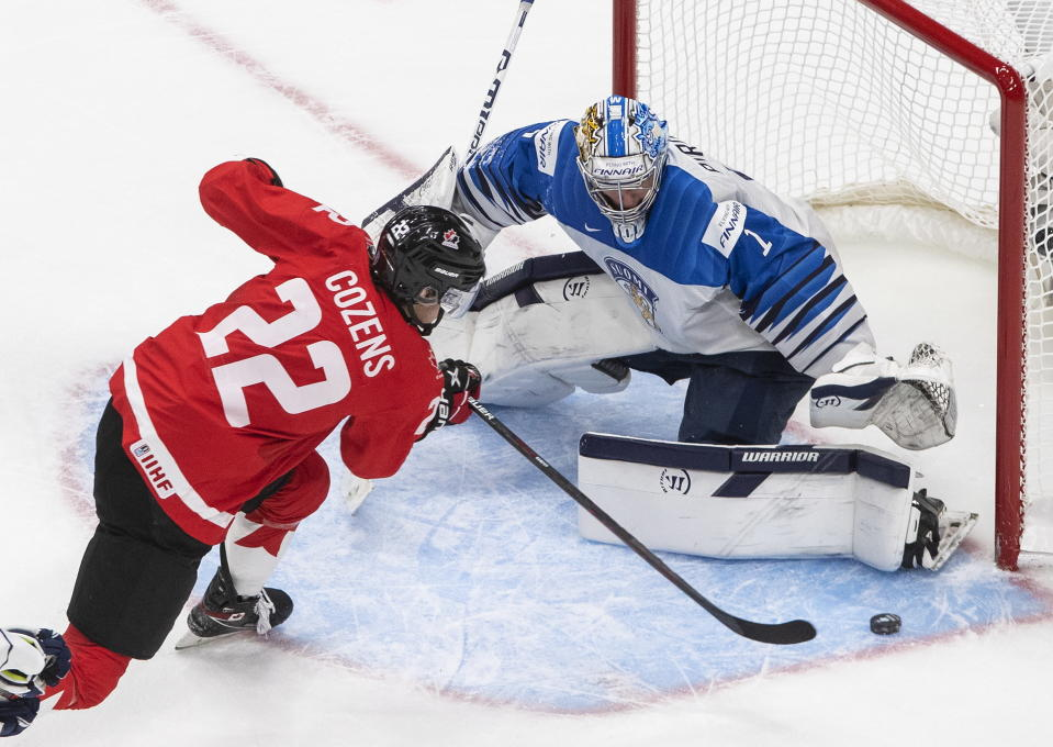 Canada's Dylan Cozens (22) is stopped by Finland goalie Kari Piiroinen (1) during the third period of an IIHF World Junior Hockey Championship game Thursday, Dec. 31, 2020, in Edmonton, Alberta. (Jason Franson/The Canadian Press via AP)