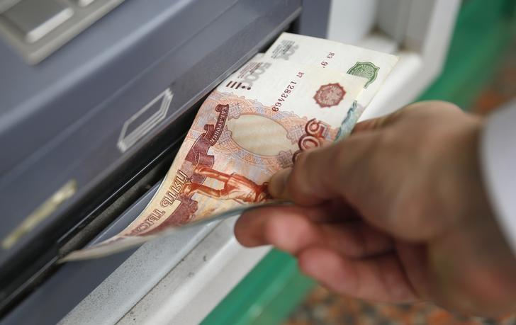 Man uses a cash dispenser to receive roubles in central Moscow