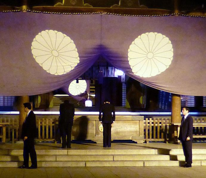 In this Sunday, April 21, 2013 photo, Japan's Deputy Prime Minister and Finance Minister Taro Aso, center right, bows as he visits the Yasukuni Shrine in Tokyo in the evening, following a visit by Keiji Furuya, state minister in charge of North Korea's past abductions of Japanese nationals, earlier in the day. Japan's Prime Minister Shinzo Abe made donations and three Cabinet ministers including Aso prayed at Tokyo's militarist shrine over the weekend, sparking South Korean anger. (AP Photo/Kyodo News) JAPAN OUT, MANDATORY CREDIT, NO LICENSING IN CHINA, HONG KONG, JAPAN, SOUTH KOREA AND FRANCE