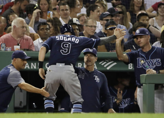 Tampa Bay Rays' Eric Sogard is congratulated at the dugout after scoring from third on a wild pitch by Boston Red Sox reliever Darwinzon Hernandez during the sixth inning of a baseball game at Fenway Park, Thursday, Aug. 1, 2019, in Boston. (AP Photo/Elise Amendola)