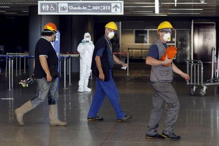 Workers wearing a mask to protect from smoke walk past a forensic investigator at the check-in desk of Terminal 3 at the international Fiumicino airport in Rome