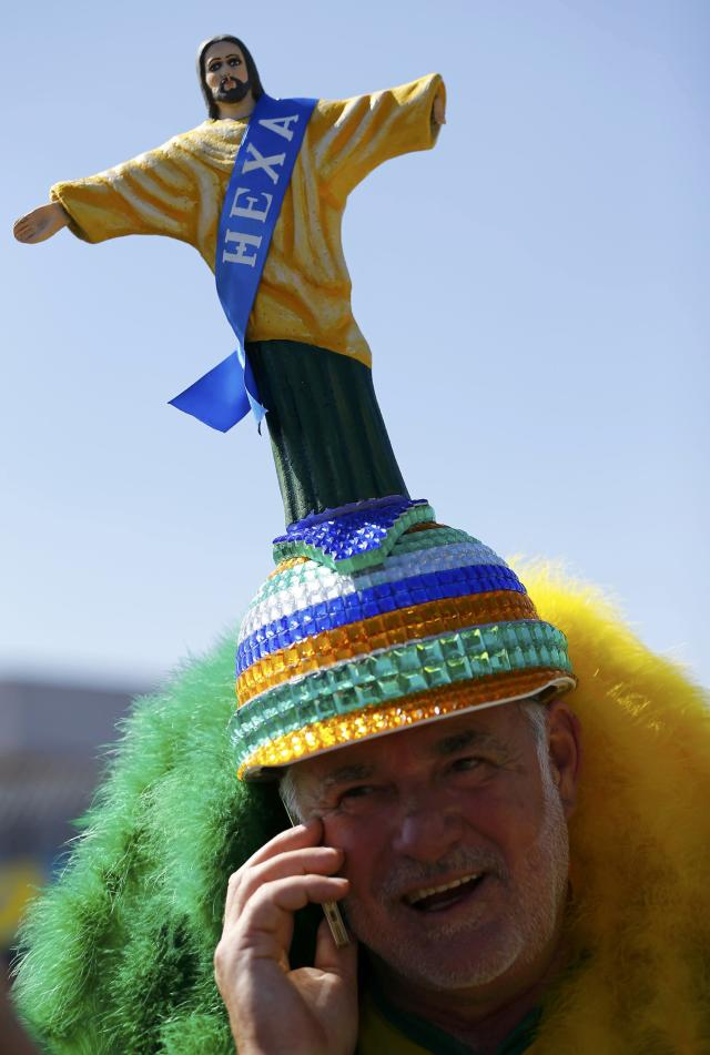 A supporter of Brazil's national soccer team makes a phone call as he arrives outside the stadium prior the opening match of the soccer World Cup between Brazil and Croatia at the Arena de Sao Paulo in Sao Paulo June 12, 2014. REUTERS/Murad Sezer (BRAZIL - Tags: SOCCER SPORT WORLD CUP TPX IMAGES OF THE DAY)