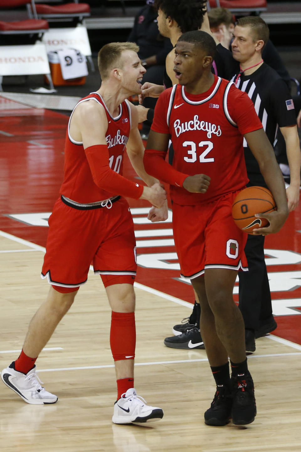 Ohio State's E.J. Liddell, right, celebrates grabbing with teammate Justin Ahrens during the second half of an NCAA college basketball game Wednesday, Jan. 27, 2021, in Columbus, Ohio. Ohio State beat Penn State 83-79. (AP Photo/Jay LaPrete)