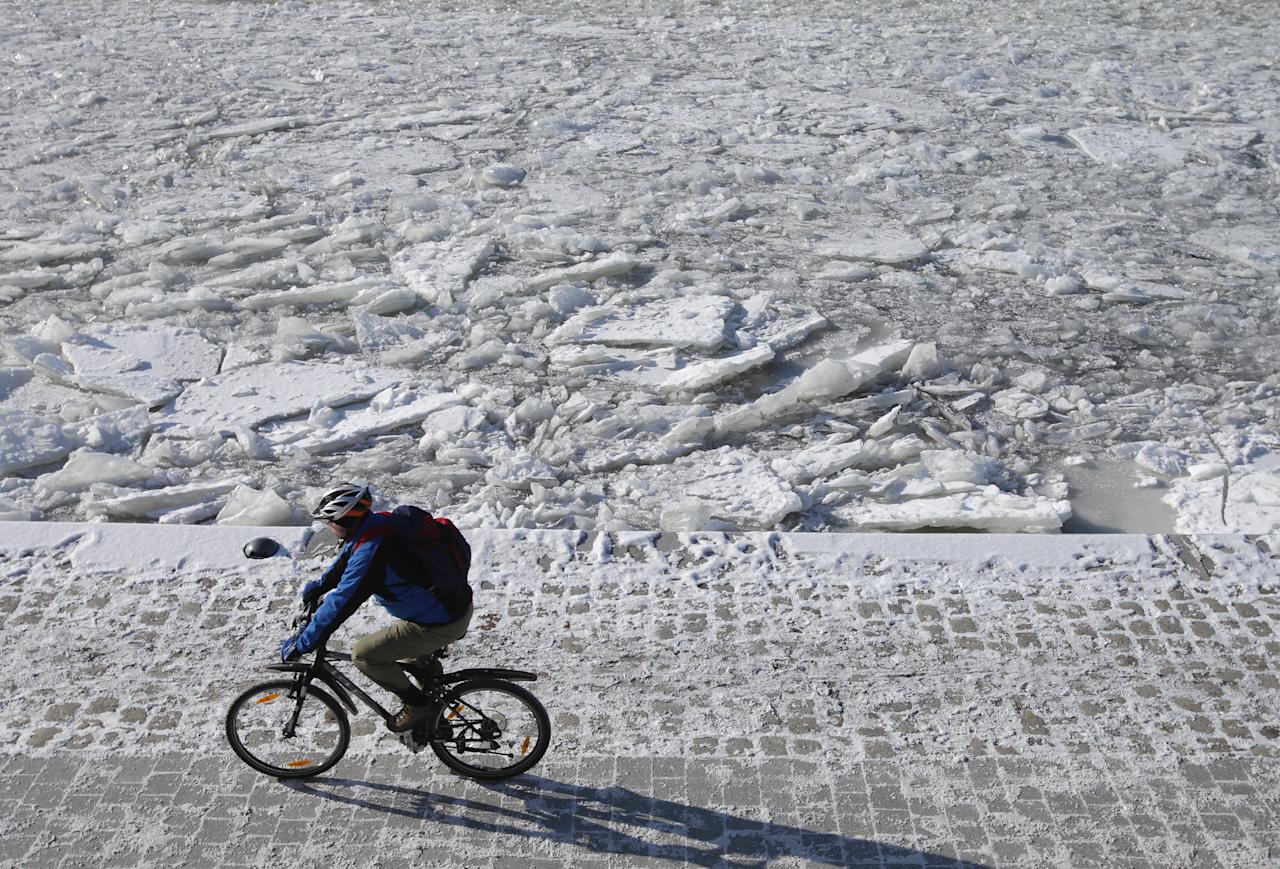 BERLIN, GERMANY - FEBRUARY 06:  A bicyclist rides past the frozen Spree river on February 6, 2012 in Berlin, Germany. Temperatures plummeted to -25 degrees Celsius in Berlin as the current cold front that has claimed over 200 lives in eastern Europe makes its way west.  (Photo by Sean Gallup/Getty Images)